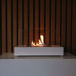 White tabletop bio ethanol fire. Designed in the shape of a table featuring glass panels. Valkoinen bioetanolitakka. Muotoiltuna